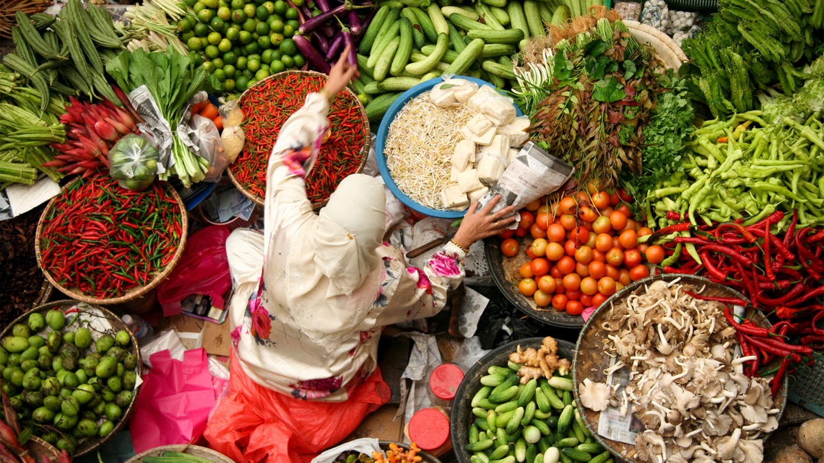 Woman sitting in fresh vegetable market