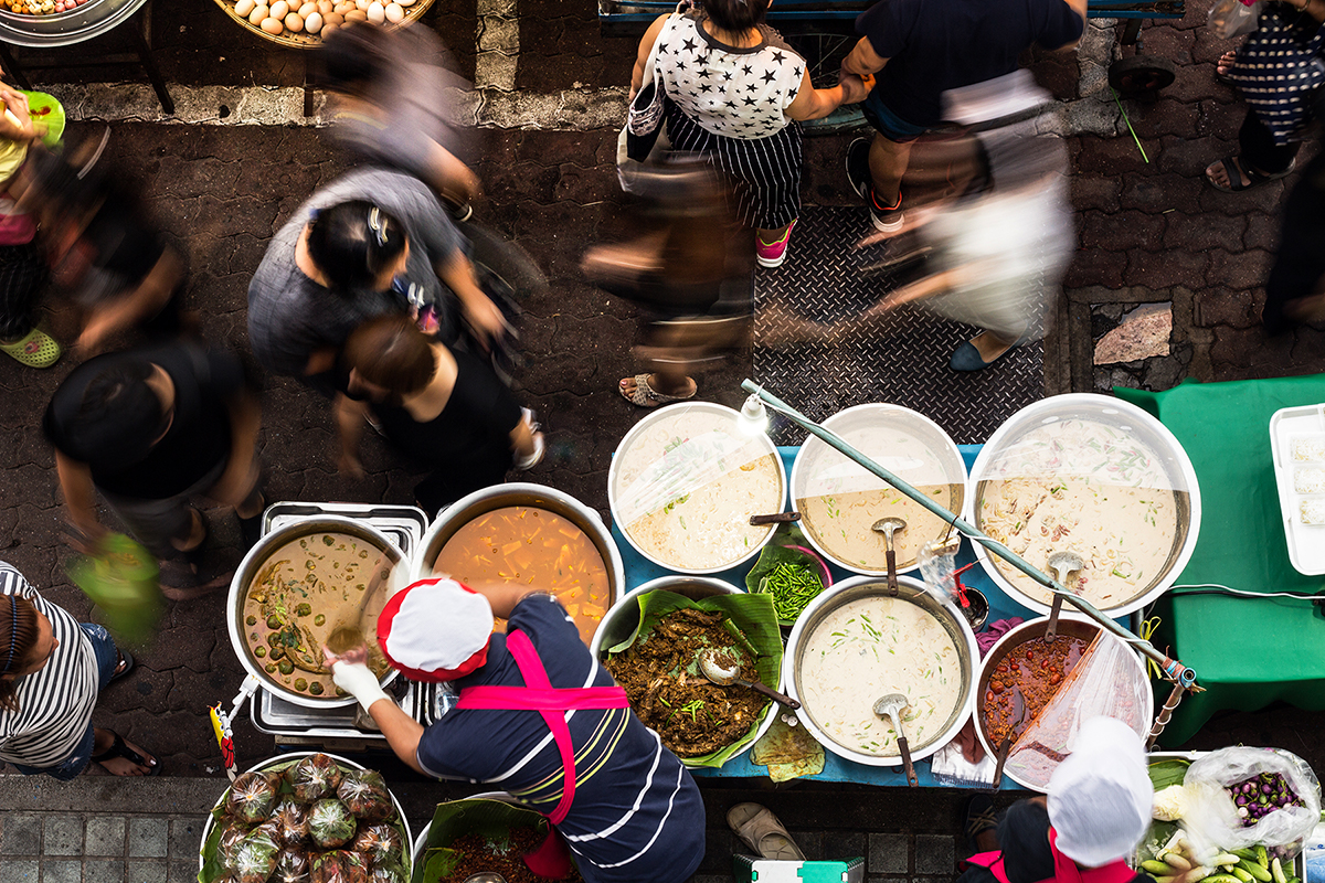 A view from above of a city street food vendor preparing food with people walking past